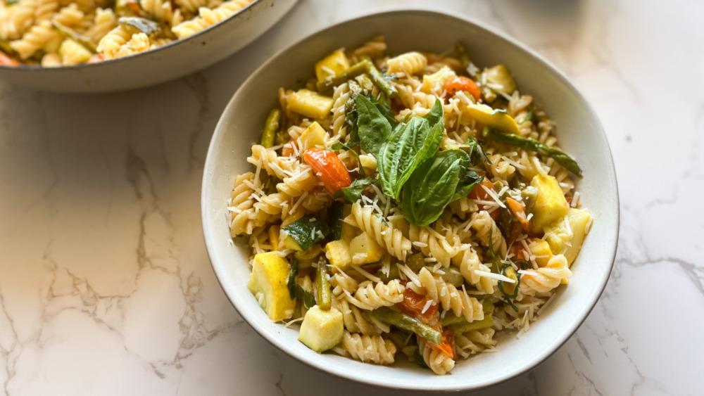 pasta primavera with noodles zucchini and tomato in white bowl