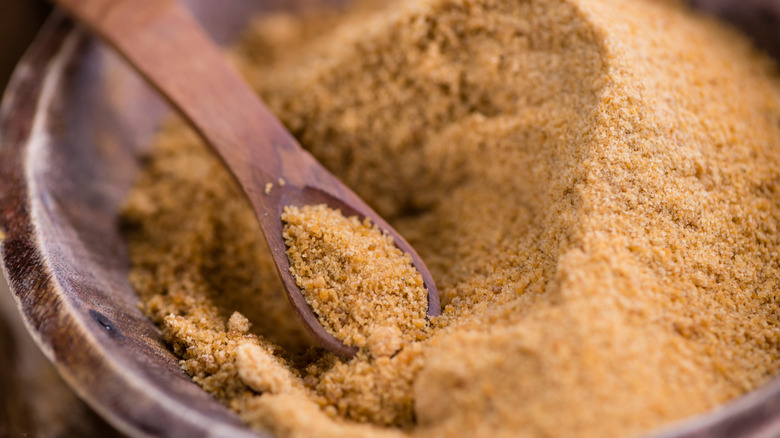 Light brown coconut sugar with wooden spoon