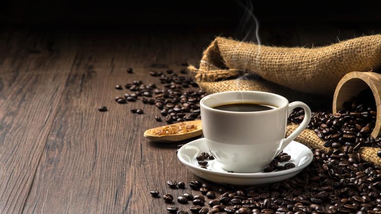 White mug of coffee next to beans
