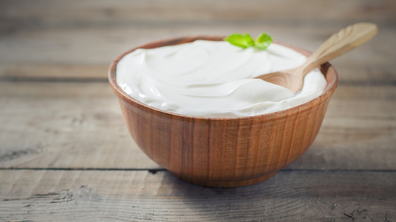 Greek yogurt in wooden bowl with spoon