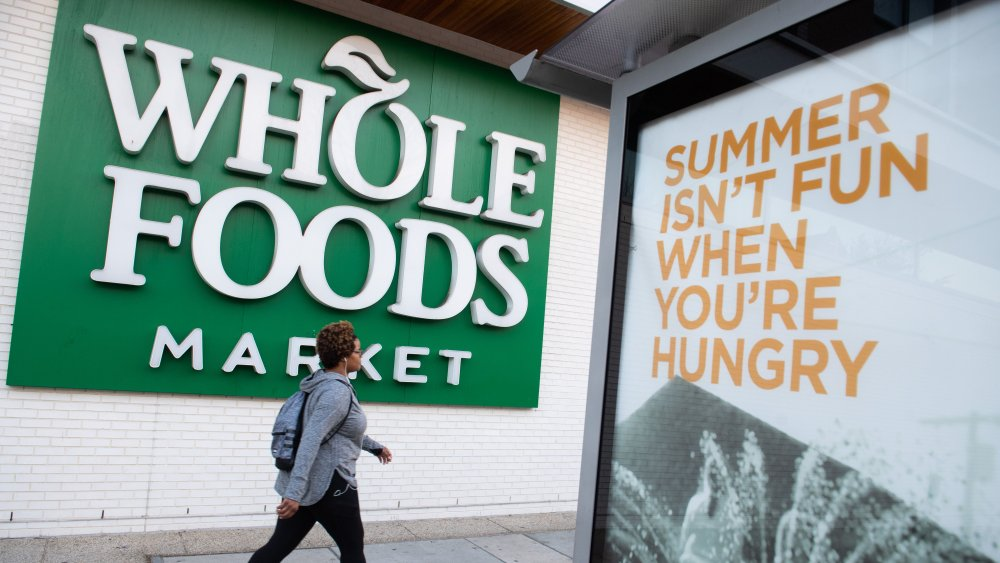 woman walking past a Whole Foods sign