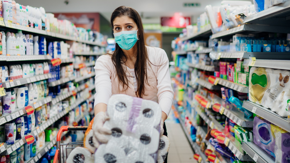 Woman buying paper towels with mask