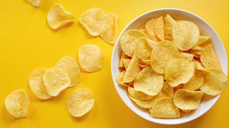 Potato chips in bowl on yellow background