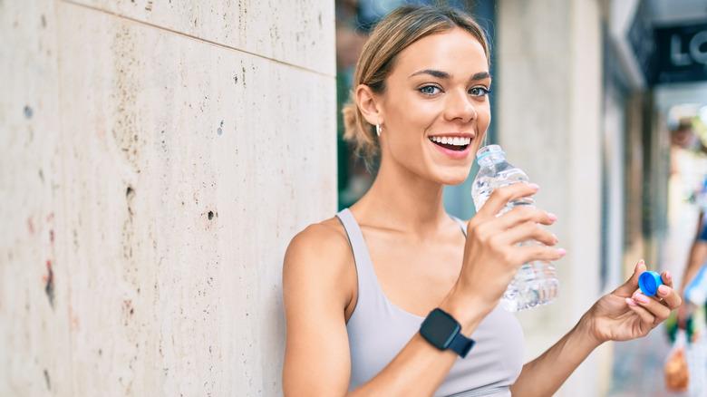 Woman drinking from plastic water bottle
