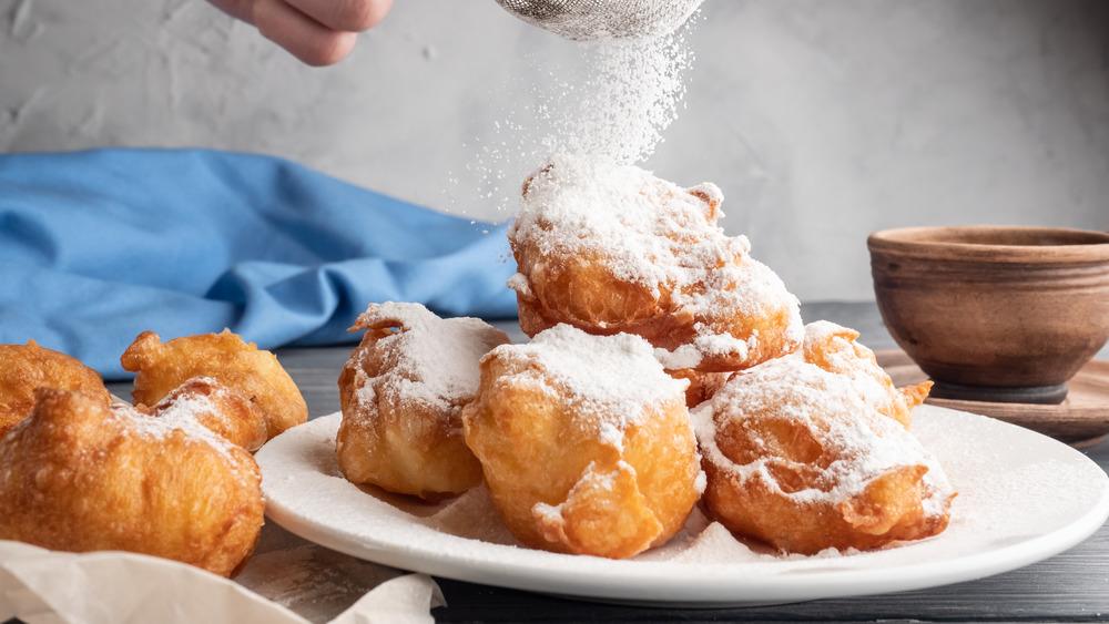 Powdering beignets