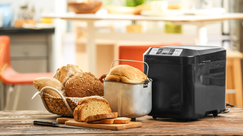 bread machine next to loaves of bread