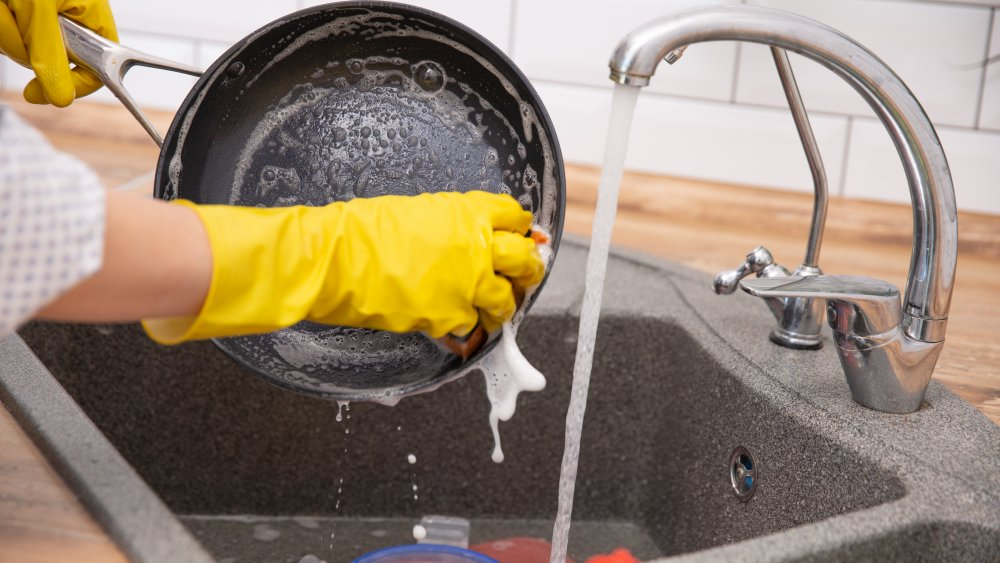 Cleaning a pan in the kitchen sink