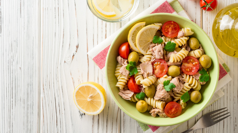 A bowl of good pasta salad with tuna, tomatoes, and lemon.
