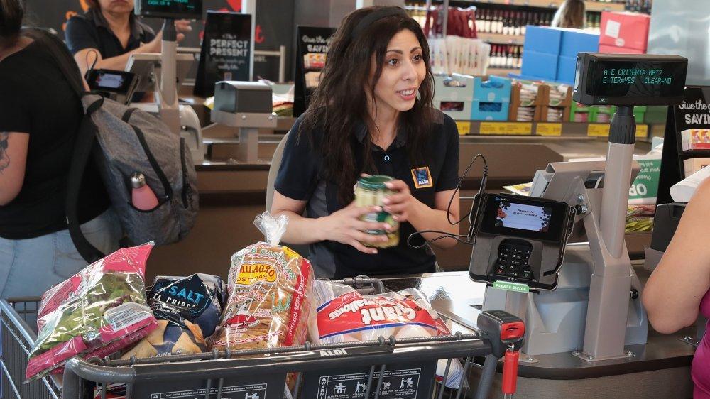 An Aldi cashier at her cash register next to a full cart.