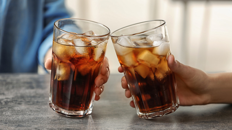 two people cheers with two glasses of cola with ice