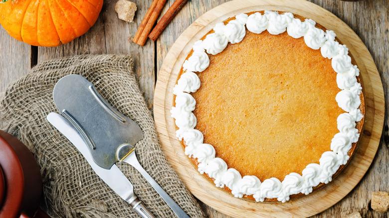 Full pumpkin cheesecake next to serving utensils