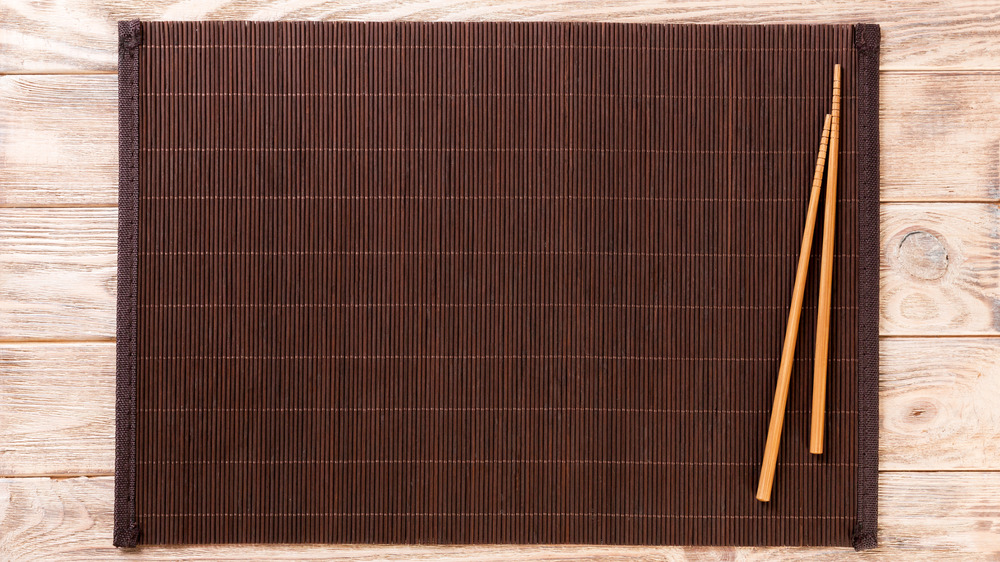 A pair of chopsticks on a brown bamboo placemat