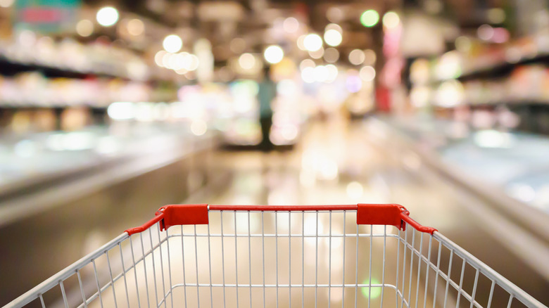 grocery cart with blurred supermarket interior in the background