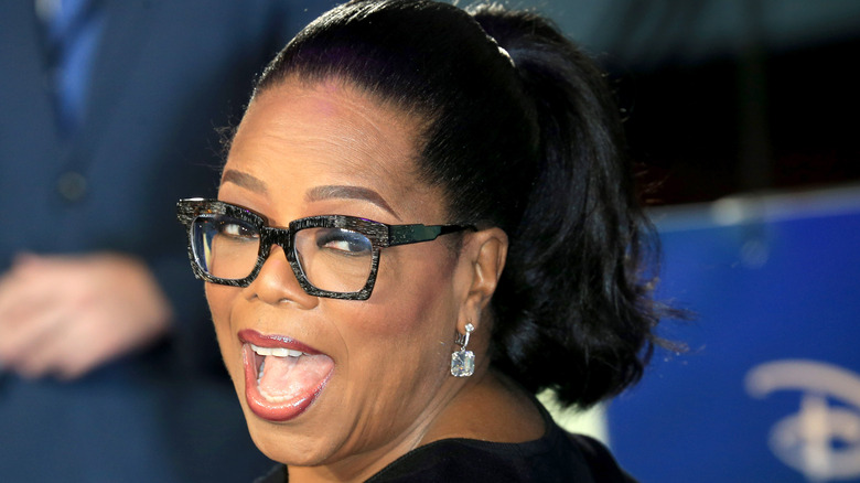 Oprah smiling with her head tilted to the side