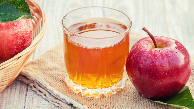 Glass of apple cider next to apples