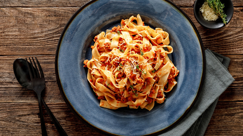 Pasta with sauce atop blue plate on wooden table