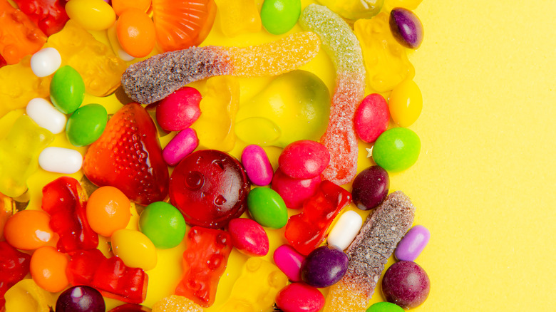 Assorted colorful candies and gummies on yellow background