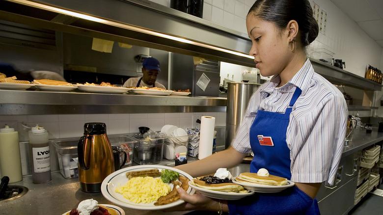 IHOP waitress picking up scrambled eggs meal