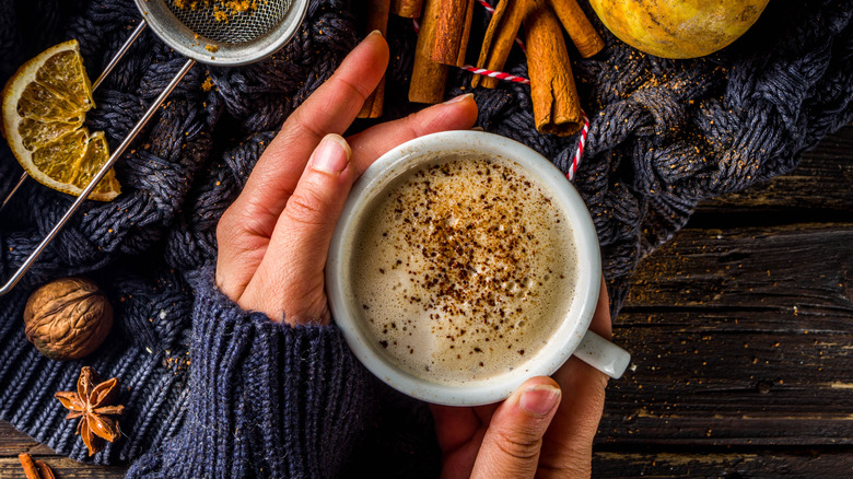 Hands holding chai with spices