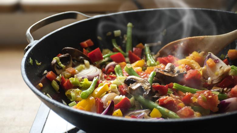 Steam frying vegetables in pan