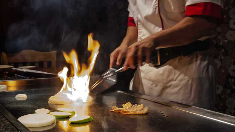 Chef cooks on teppanyaki grill