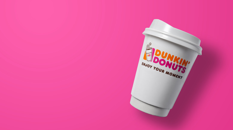A Dunkin cup with logo on pink background