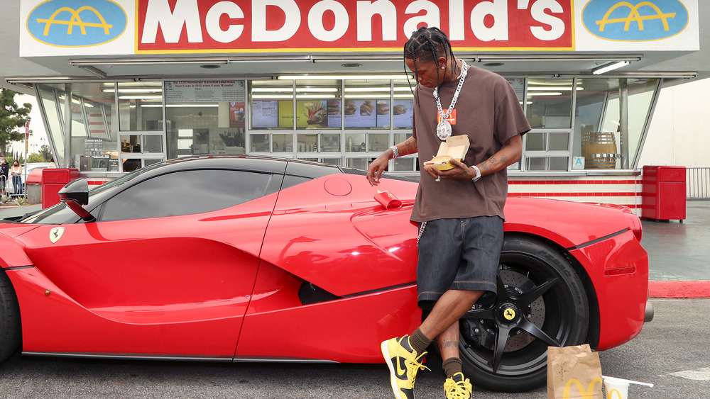 Travis Scott and his red Ferrari outside McDonald's