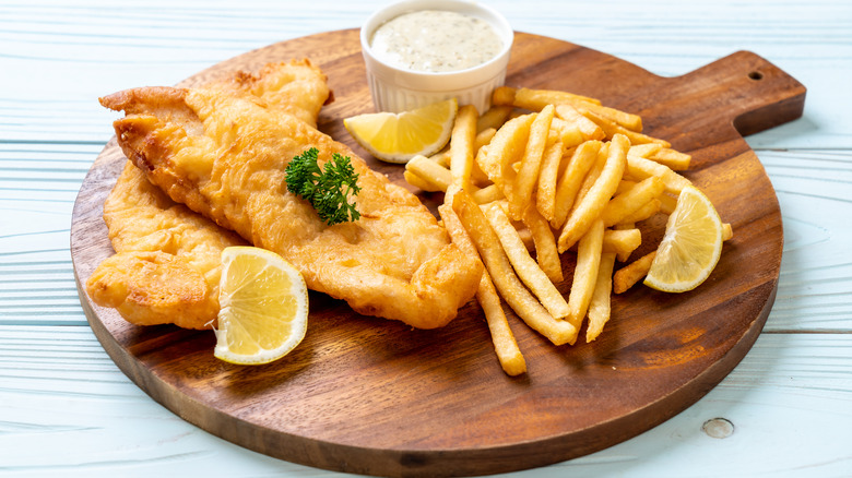 Fried fish and chips on wooden board