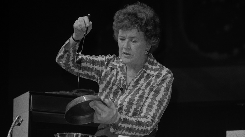 Julia Child holding a spoon and kitchen pan against a black background
