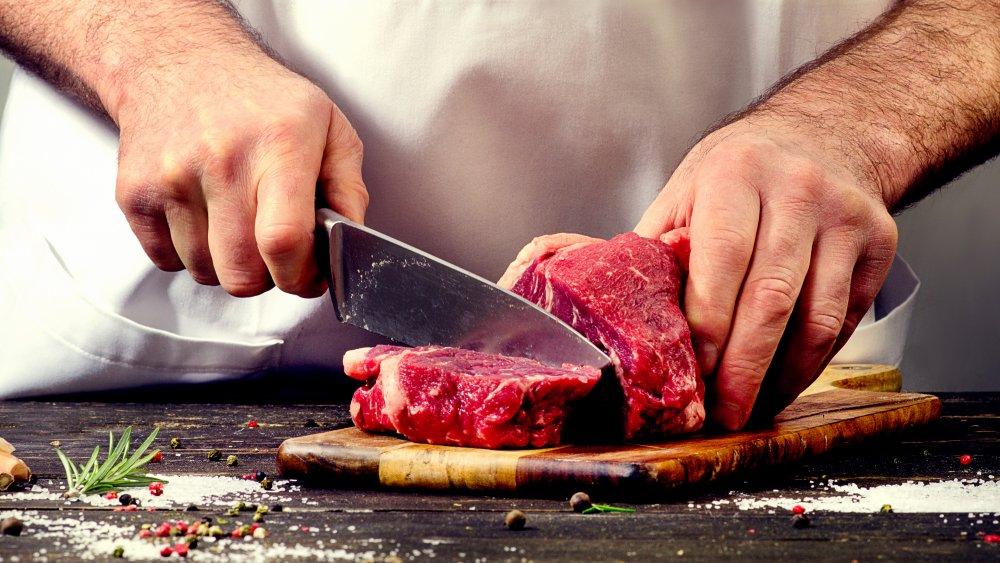 man slicing up steak