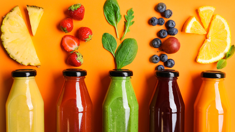 Line of fruits and juices in bottles
