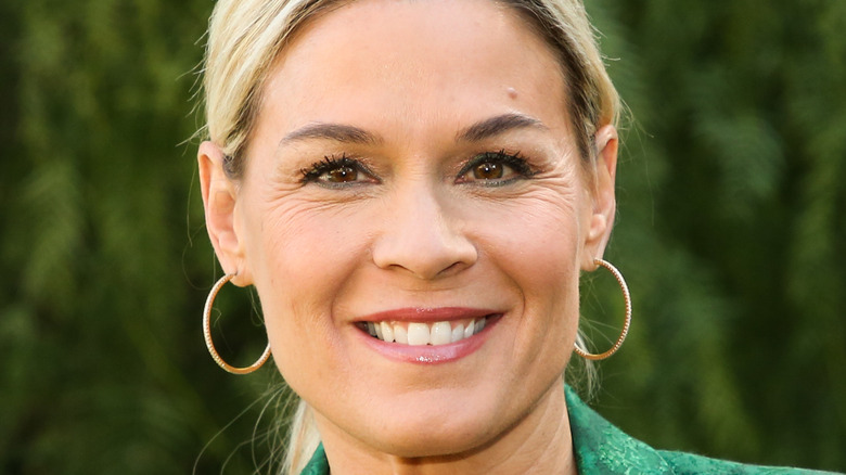 Cat Cora smiling with hoop earnings