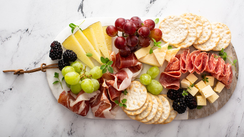 Charcuterie board with assorted cheeses, meats, and fruits