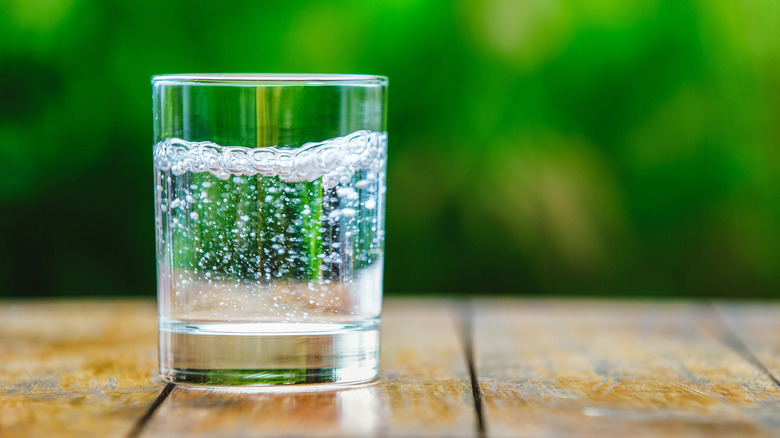 Glass of sparkling water on wooden table