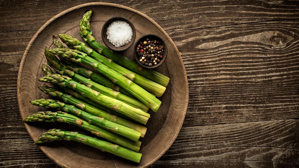 Fresh asparagus in wooden bowl