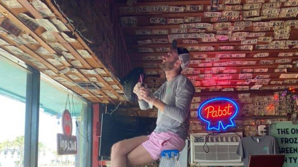 Man helping take down dollar bills at Sand Bar