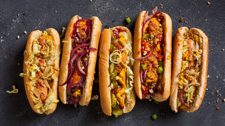 A row of hot dogs on gray slate