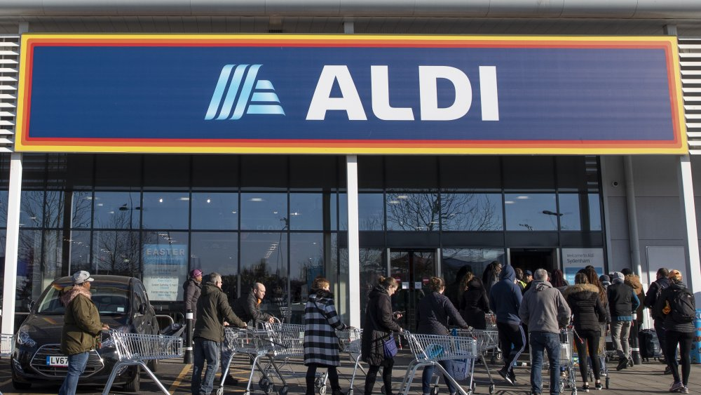 Shoppers waiting in front of an Aldi store