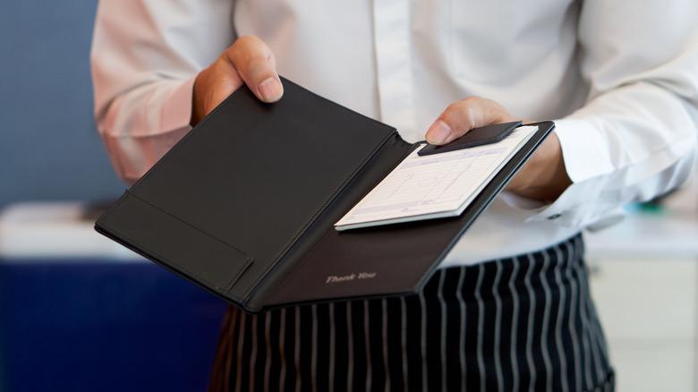 A restaurant server with a receipt