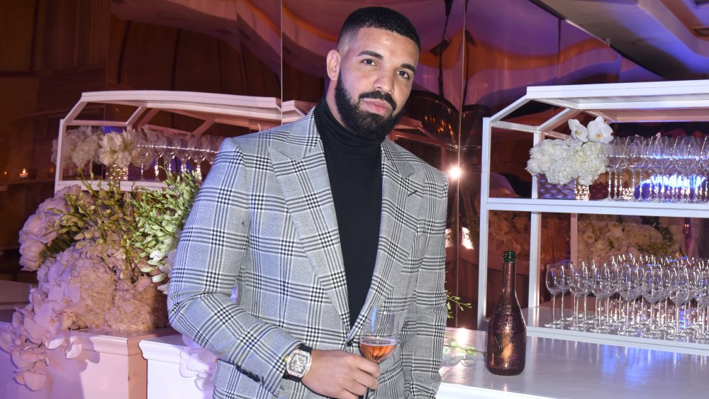 Drake enjoying himself at a party with a glass of rose