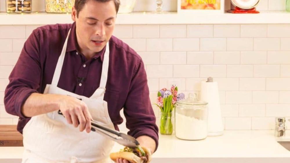 Jeff Mauro putting giardiniera on an Italian beef sandwich