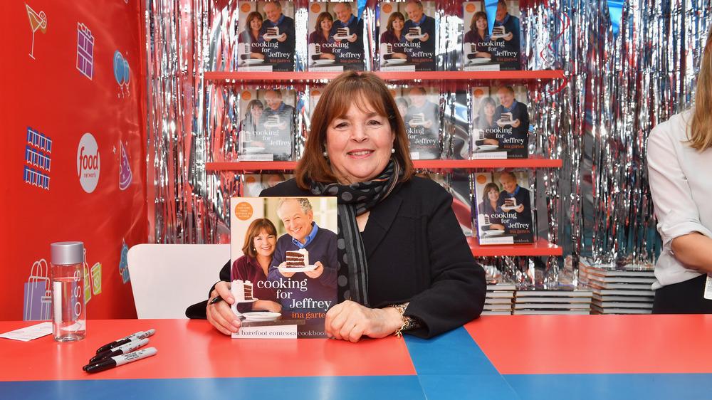 Ina Garten holding up a cook book