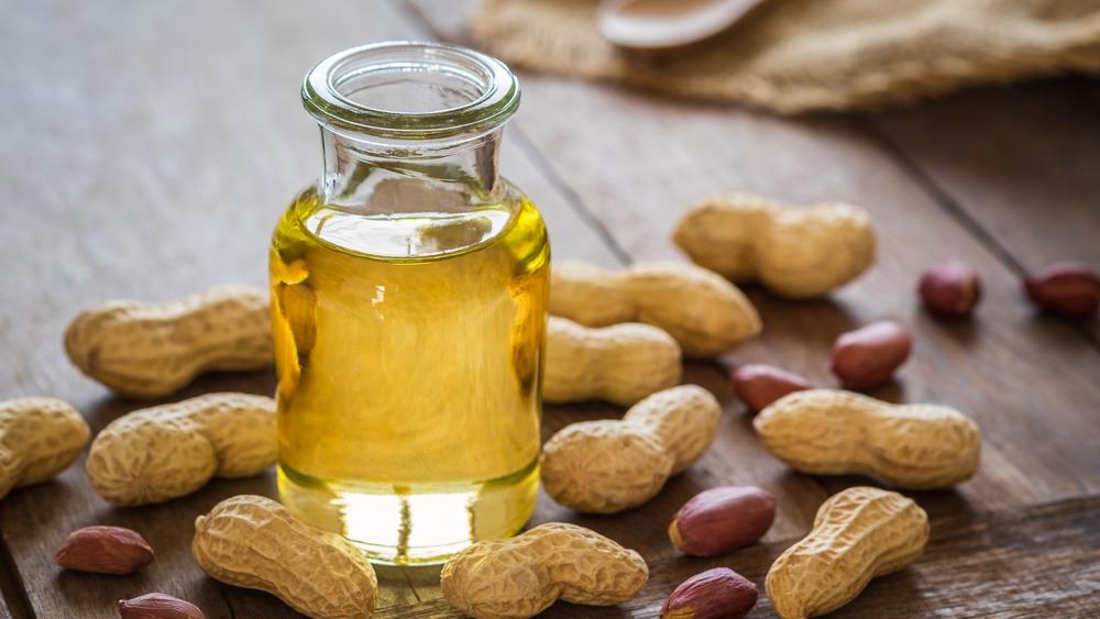 Peanut oil bottle and peanuts