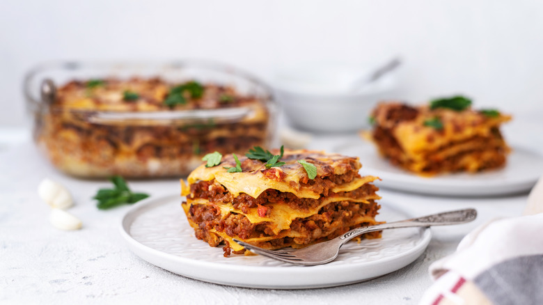 cooked lasagna with two plates of sliced lasagna