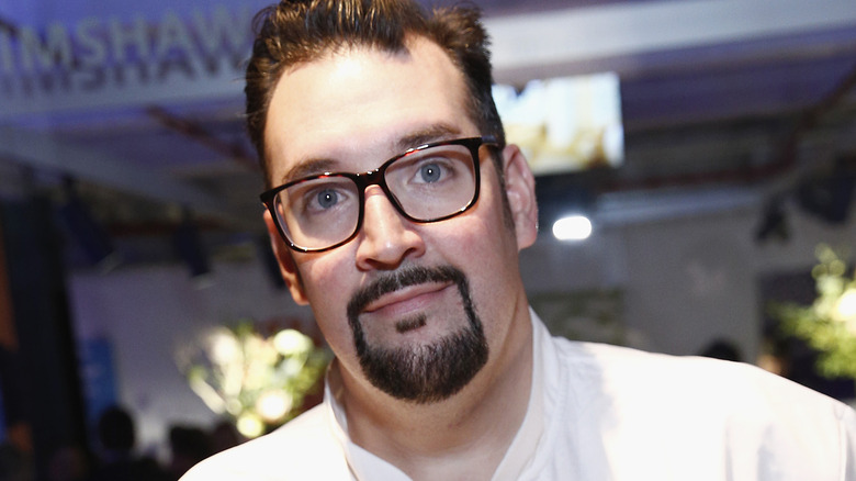 Michael Vignola looks forward in black framed glasses and a goatee