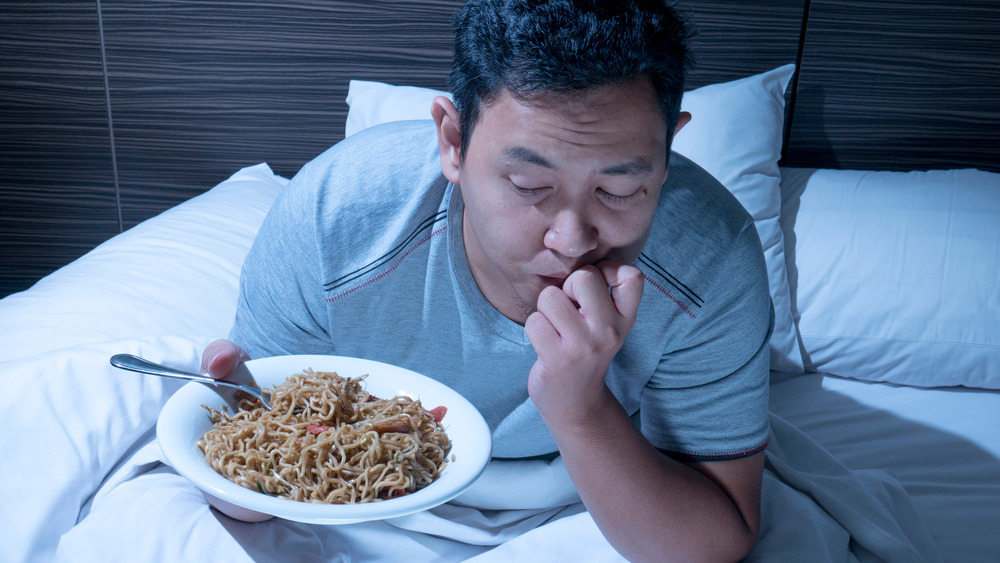 Man eating noodles in bed