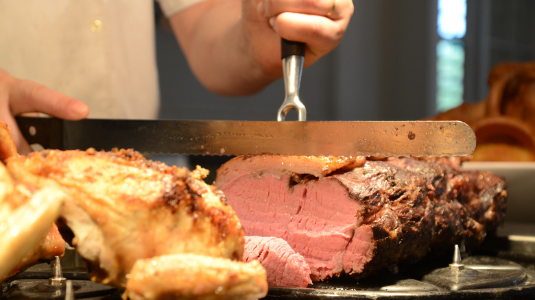 man carving red meat
