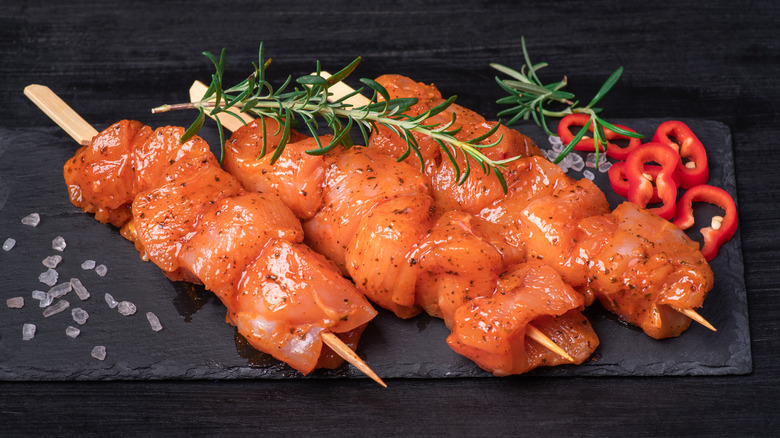 Chicken skewers in a marinade on a black plate
