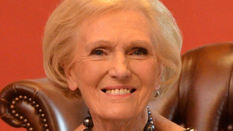 Mary Berry sitting at desk with her cookbooks