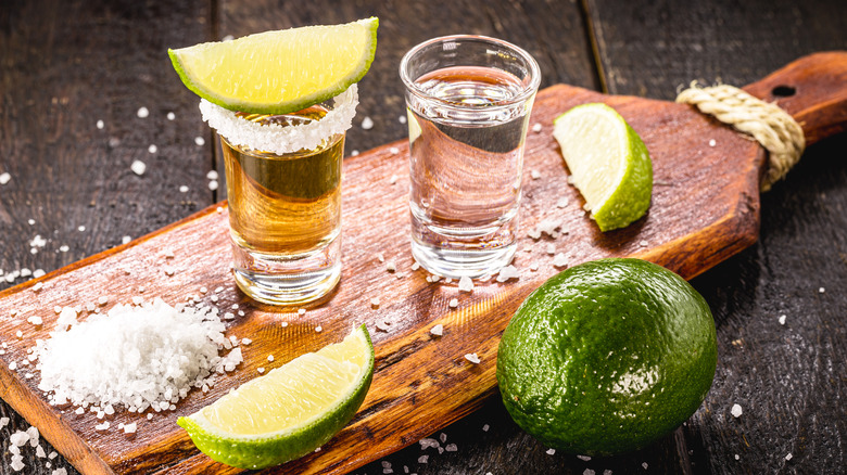 Shots of tequila on cutting board